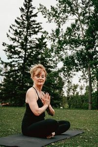 Frau mit Namaste Mudra auf Yoga-Matte im Park