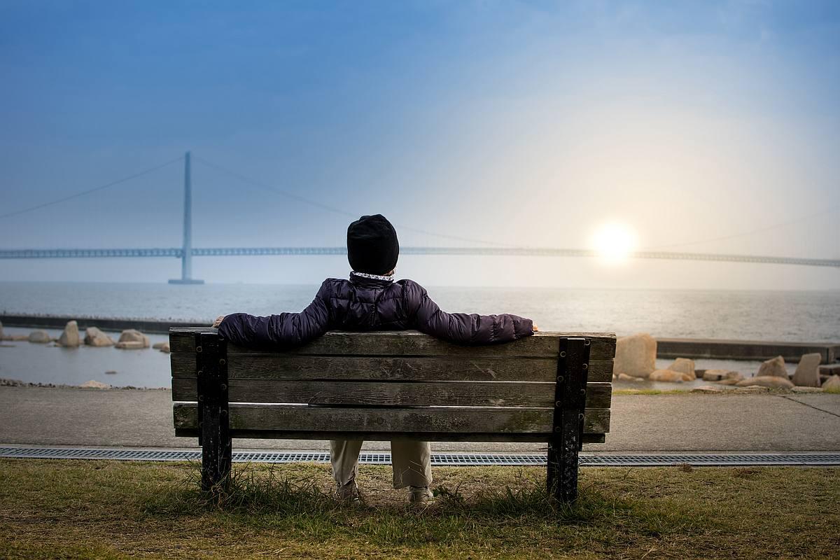 Mann sitzt auf Bank vor einem Gewässer und genießt die Stimmung